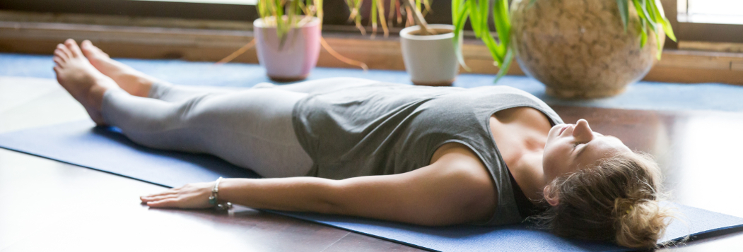 Woman lying on her back on a yoga mat relaxing with plant pots in the background